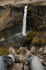 Anonymous man Feet on a waterfall background of Iceland, man seat on the cliff looking at the waterfall from above