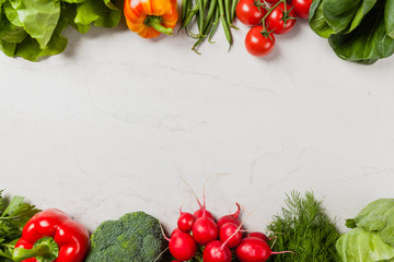Stone background with a border of fresh vegetables.