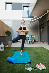Woman doing yoga on the backyard of her apartment.