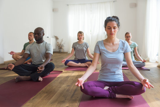 Group of people doing meditation in yoga class