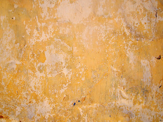 peeling layers of yellow and beige paint on a cement wall with cracks and random splashes of other colors