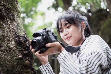 Asian photographer photoshoot working camera. Woman taking photo with smiling for hobby and lifestyle with green trees in forest at outdoor.