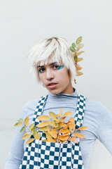 Portrait of a Young Woman in Checkered Overalls Posing with Adorable Yellow Leaf Accessories
