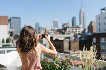 Young woman taking a picture of skyline