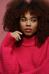 Portrait of a young African American afro woman in pink studio