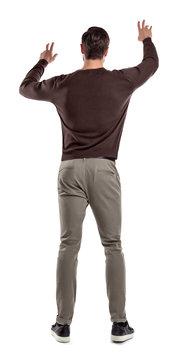 A fit man in casual sweater stands in a back view with both arms lifted up to manipulate an invisible touch screen.