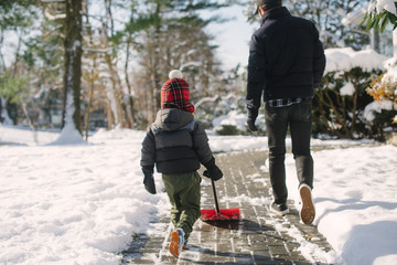 Little kid shoveling snow with dad