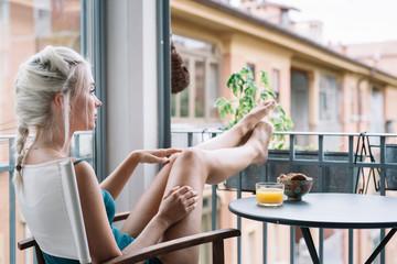Woman enjoying view from window having breakfast