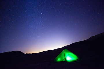 A tent glows under a night sky full of stars. Timna national Park, Israel