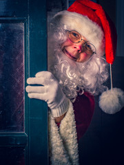 Portrait of amusing Santa Claus  looks out of the door Merry and cozy Christmas at home concept.