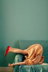 Side view of woman bending on couch