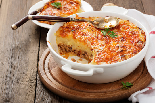Shepherd's pie, traditional British dish with minced meat and mashed potato on rustic wooden table.
