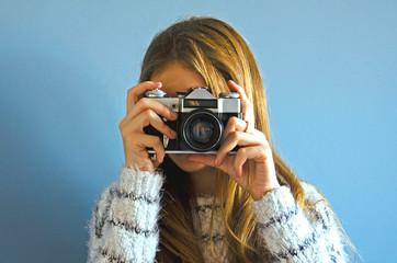 A girl is taking pictures on an old camera. Vintage camera on film