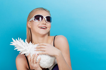 Young blond woman in blue bikini on blue background, with sunglasses and white pineapple