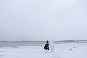 Cosmonaut with fir tree in snows