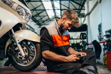 Mechanic using a phone in the motorbike workshop