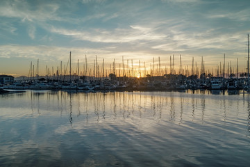 Sun setting on Emeryville Marina. Sailboats moored in San Francisco Bay with sunset skies and water reflections. Alameda County, California, USA.