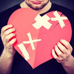Very sad man holding broken heart