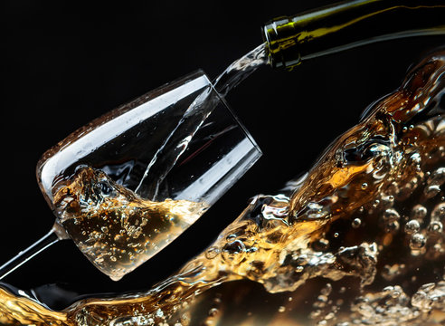 White wine being poured into wineglass on a black background.