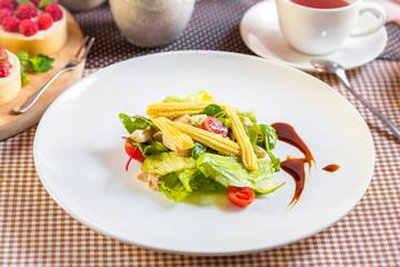 Salad with corn, arugula, algae, tomatoes and greens