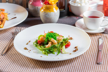 Salad with shrimps, arugula, algae, tomatoes and greens