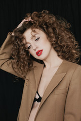 Portrait of charming young curly woman posing indoors on black