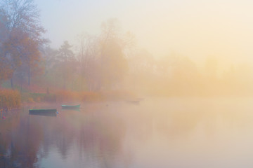 Boats floating on a calm misty lake. Stylized for a retro photo (with grain). Masuria, Poland.