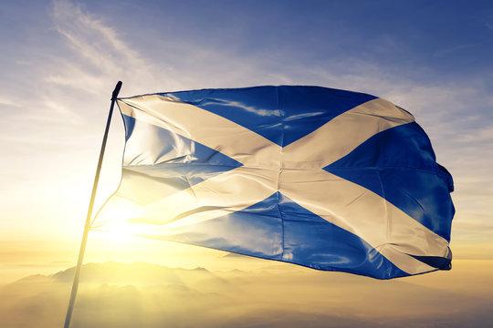 Scotland scottish flag textile cloth fabric waving on the top sunrise mist fog