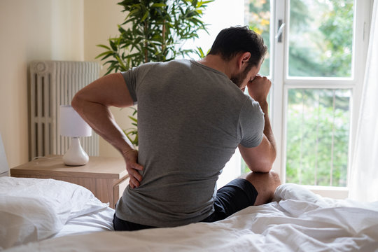 Man waking up in the morning and suffer for back pain