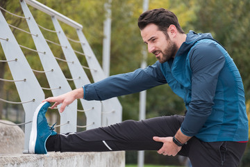 Man with sportive clothes doing leg stretches exercises