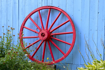 Old Red Wagon Wheel on Blue Barn