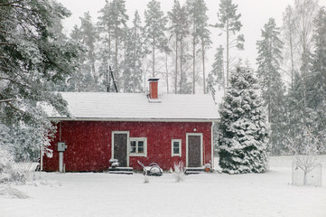 Small red cabin in heavy snowfall