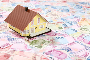 Real estate for sale concept with model house over Turkish Lira background.