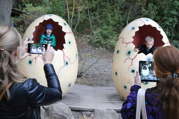 Women take photos of children during a dinosaur exhibition at the Nikitsky Botanical Garden outside Yalta