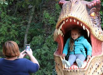 A girl poses for a photo during a dinosaur exhibition at the Nikitsky Botanical Garden outside Yalta