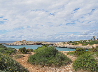 a stone path with a view of the coastline and the old british era Torre des Castellar at the edge of the bay in cala santandria near cuitadella with bright blue sea and summer cloudsidy