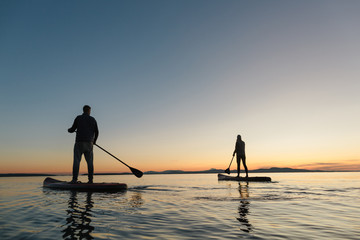 Couple stand up paddle boarding together at sunrise