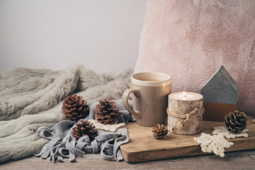 Hygge Scandinavian style concept with coffee cup, candles and pine corn