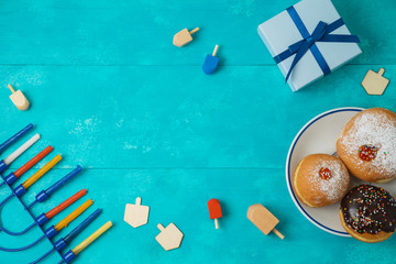 Jewish holiday Hanukkah concept with menorah, sufganiyot, gift box and spinning top