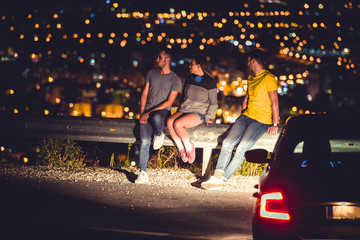 Friends sittinig on road guardrail at night