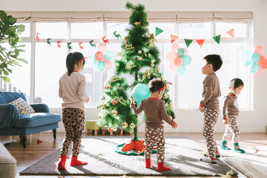Kids decorating christmas tree at home