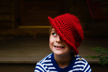 little boy taking a silly pose with a red wooly hat