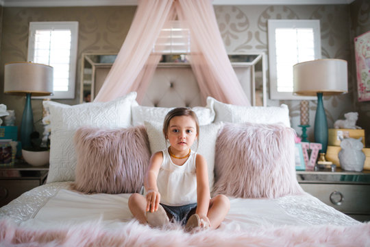 Young little girl sitting on pink princess bed in her room