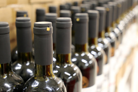 Wine bottles in a row, shallow depth of field. Liquor store, wine production concept
