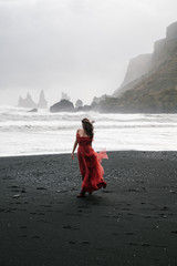 yang women in a red long dress walks on the black sand beach, VIk Iceland