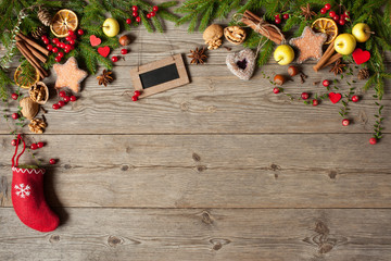 Christmas wooden background with fir branches, a sock with a gift, apples, cookies and red berries