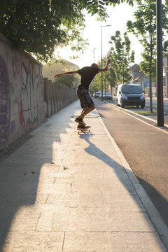 Teenager riding skateboard on the sidewalk