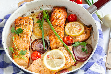 Salmon fried in a pan with onions, lemon and cherry tomatoes