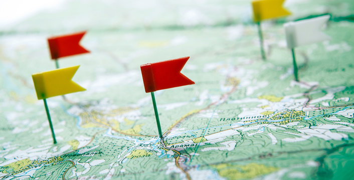topographic map with colored flag pushpins close up