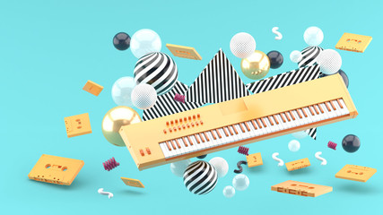 Orange piano keyboard and orange tape amidst colorful balls on a blue background.-3d render..